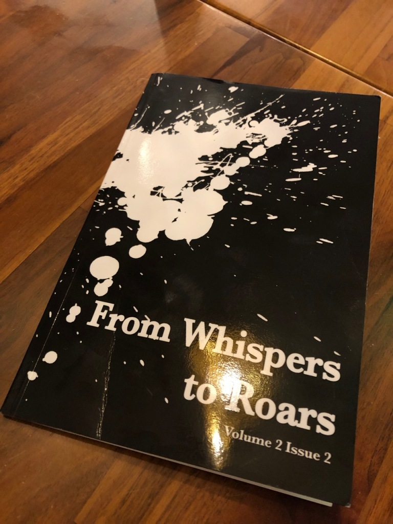 From Whispers to Roars Volume 2 Issue 2 cover with white splatters on a black background