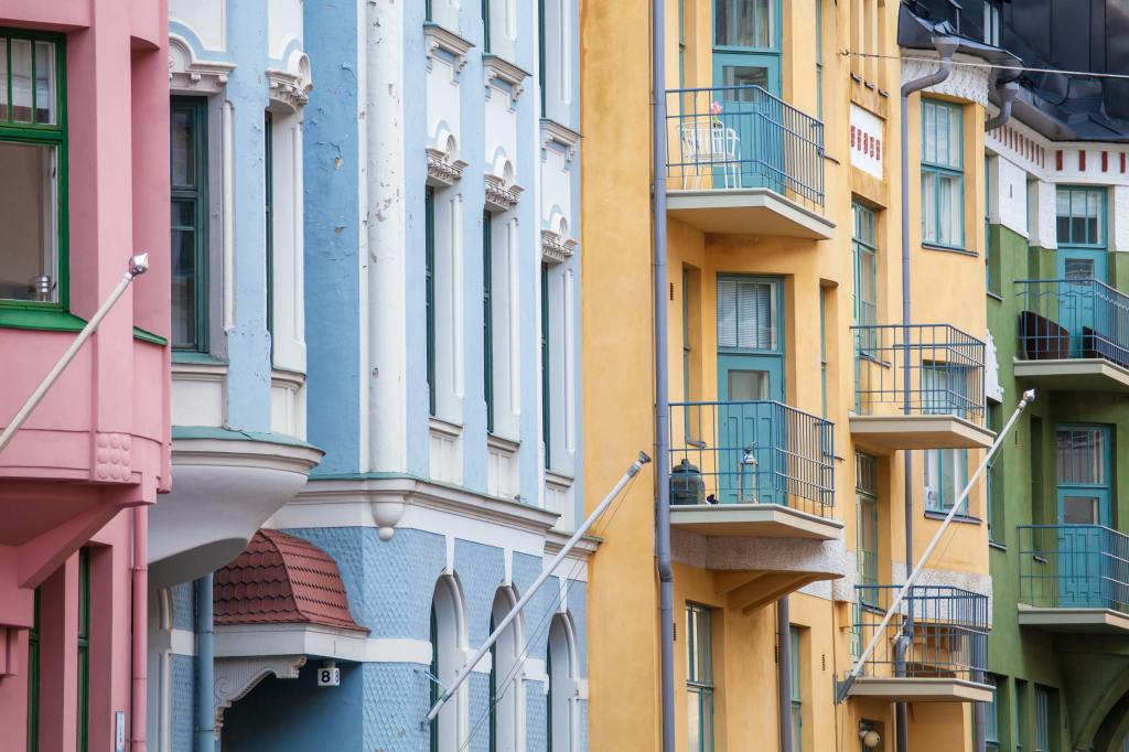 Photo of three-story, pastel-colored buildings with empty balconies by Tapio Haaja on Unsplash